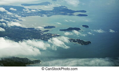 Aerial View of Thailand's Beautiful Coastline through Puffy Clouds