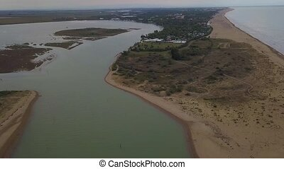 Aerial view of the beautiful lagoon of Caorle towards Bibione in Italy with people enjoying summer at the beach and boats passing by.