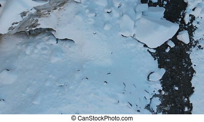 Aerial view of the birth of a mountain river in a glacier....