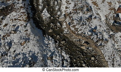 Aerial view of the birth of a mountain river in a mountain gorge. River. Winter view of a mountain river in the mountains. View from above