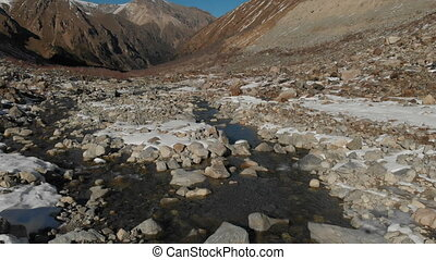Aerial view of the birth of a mountain river in mountain gorge. The river. Winter view mountain river in the mountains