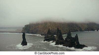 Aerial view of the black volcanic beach and troll toes cliffs in Iceland. Mountain on background covered with white fog.