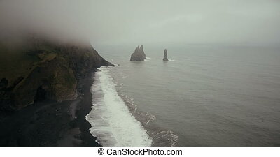 Aerial view of the black volcanic beach and troll toes mountain in Iceland. Beautiful landscape of sea, waves and fog.