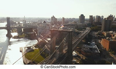 Aerial view of the Brooklyn bridge and district in New York, America. View of the flag waving on wind and East river.