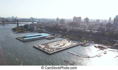 Aerial view of the Brooklyn bridge through the East river to Brooklyn district. Drone flying over the pier on the shore