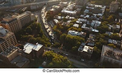 Aerial view of the Brooklyn district in New York, America, Drone flying over the apartments and traffic road on sunset.
