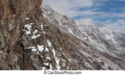 Aerial view of the close span of the camera next to a rock wall high in the mountains in early spring green grass and snow on the slopes of the mountains.