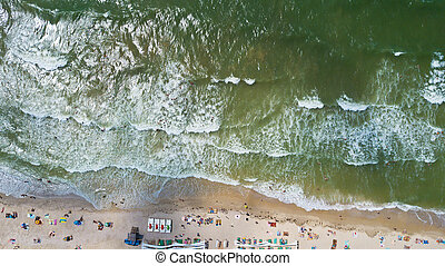 Aerial view of the coastline with a beach and sea with waves - top