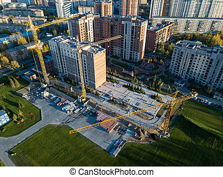 Aerial view of the construction site of a building in the industrial center of the city among buildings located close to each other with three yellow high elevating cranes by a green lawn with grass