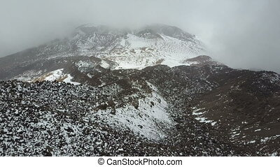 Aerial view of the crater of a volcano pico Viejo on Tenerife, covered with snow and clouds.