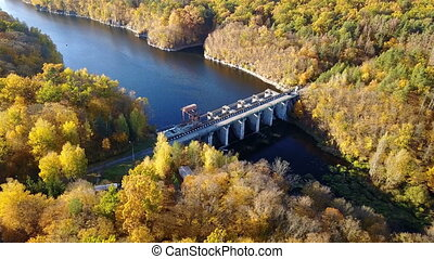 Aerial view of the dam on river with trees covered yellow...