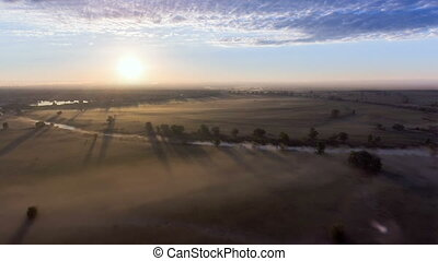 Aerial view of the dawn over the field in the fog.