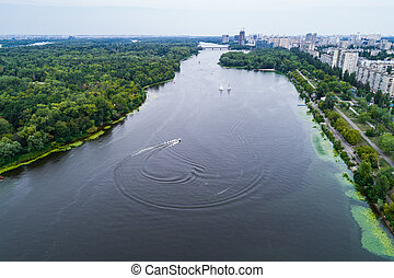 Aerial view of the Dnieper River with a high-speed motor boat that discharges water circles