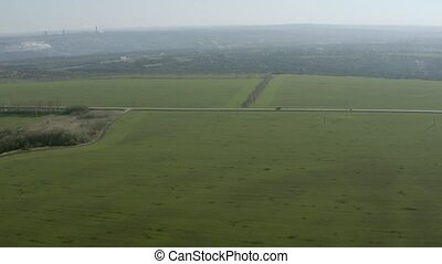 Aerial view of the field and the road with cars in the distance.