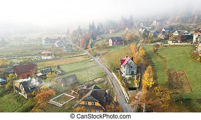 Aerial view of the field at mountains with a morning fog