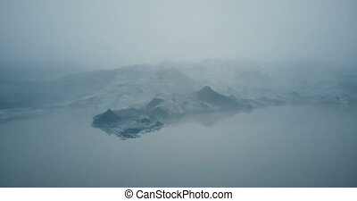 Aerial view of the glacier Myrdalsjokull in Iceland. Copter flying over the melting iceberg in foggy valley in the lake.