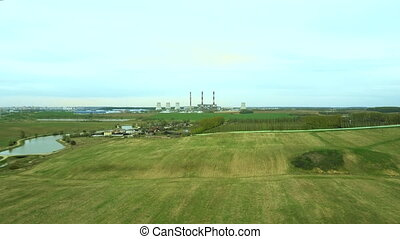 Aerial view of the green field and industrial factory. Flight over the plant producing thermal energy with pipes.