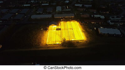 Aerial view of the greenhouse with bright light shining...