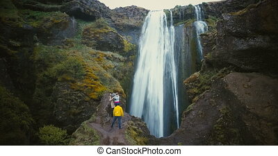 Aerial view of the group of tourists enjoying the view of Gljufrabui waterfall in Iceland. Friends happy after hiking.