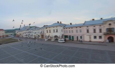 Aerial view of the historical center of Zhovkva, Lviv region, Ukraine. Perfect city. Shooting with FPV drone. Flock of birds flies around the drone