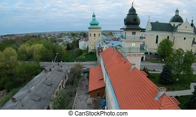 FPV drone flies maneuvering along the historic center of Zhovkva, Lviv region, Ukraine. Aerial view