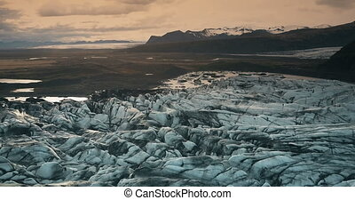 Aerial view of the ice lagoon on sunset. Copter flying over the glacier Vatnajokull with volcanic ash in Iceland.