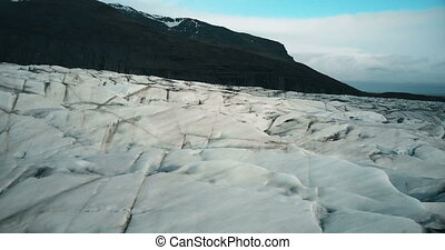 Aerial view of the ice valley, glacier Vatnajokull with black volcanic ash. Copter flying over the iceberg in Iceland.