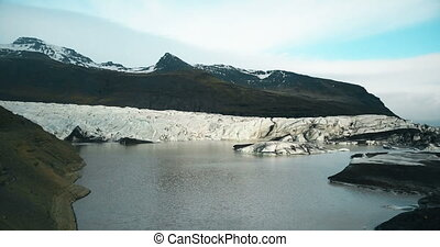 Aerial view of the iceberg valley with lake. Copter flying...
