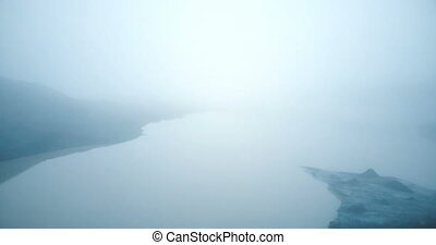 Aerial view of the lake and glacier Myrdalsjokull in Iceland. Copter flying over the iceberg and water in fog.