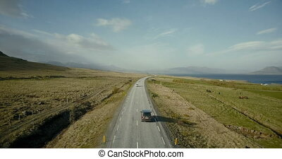 Aerial view of the mountains road. Cars riding through the...