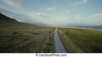 Aerial view of the ocean and mountains valley. Cars riding...