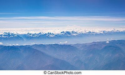 Aerial view of the Peruvian Andes, shot from aeroplane. High altitude mountain range and glaciers. Expansive view.
