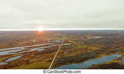Aerial view of the road in a field with lakes and forests at dawn (North Shoal Lake, Manitoba, Canada)