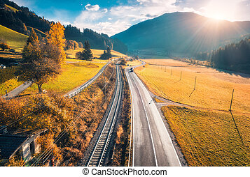 Aerial view of the road in mountain valley at sunset in autumn