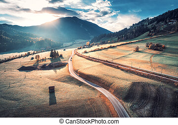 Aerial view of the road in mountain valley at sunset