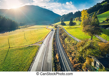Aerial view of the road in mountain valley at sunset in spring