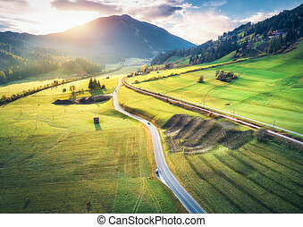 Aerial view of the road in mountain valley at sunset in summer