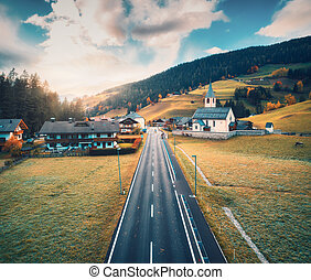 Aerial view of the road in the village in mountains at sunset