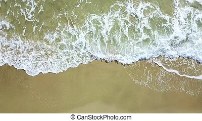 Aerial view of the sea waves crashing on the beach. Aerial survey. Slow motion