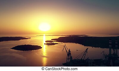 Aerial view of the shipyard and the sea harbour at sunset