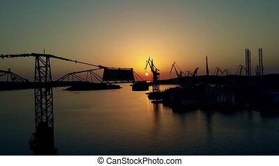 Aerial view of the shipyard, tower crane and the sea harbour at sunset