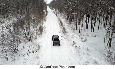 Aerial view of the SUV 6x6, riding on a snow-covered road in winter forest, back view