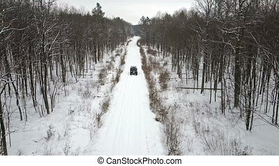 Aerial view of the SUV 6x6, riding on a snow-covered road in winter forest,  front view