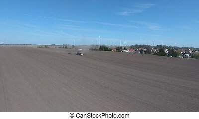 Aerial view of the tractor harrowing a large brown field in spring season