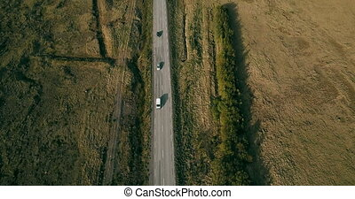 Aerial view of the traffic road. Cars goes through the motorway on the beautiful countryside green field.