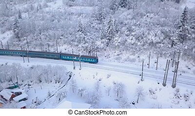 Aerial view of the train going through the mountainous...