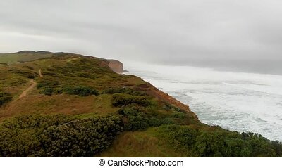 Aerial view of the Twelve Apostles, a collection of limestone stacks off the shore of Port Campbell National Park from Gibson Steps on a cloudy day.