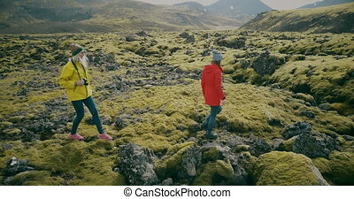 Aerial view of the two woman walking on the lava field in...