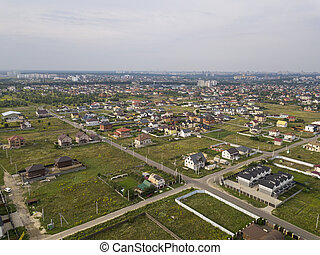 Aerial view of the village against the background of the far-sighted city on a summer day