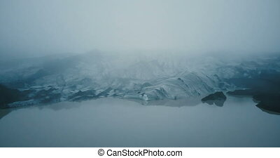 Aerial view of the white glacier Myrdalsjokull with black ash in Iceland. Eternal ice in fog in mountain.